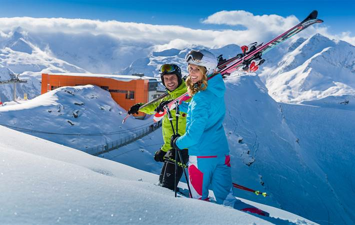 Couple in ski outfit standing on ski slope in front of mountain panorama